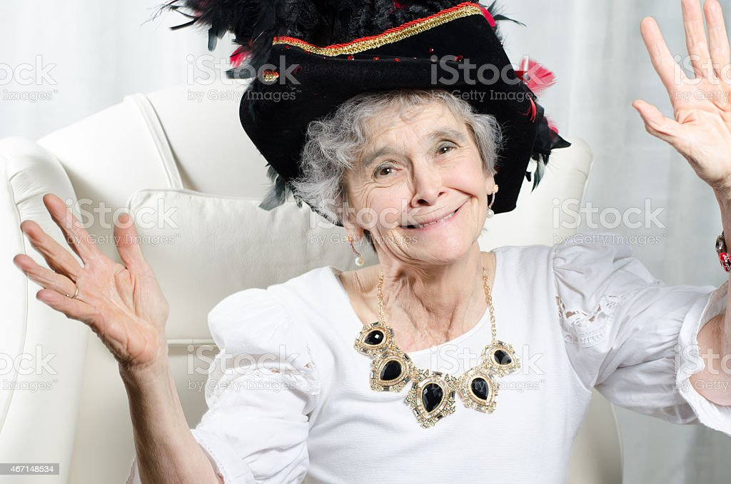 old woman with carnival hat cheers for carnival stock photo