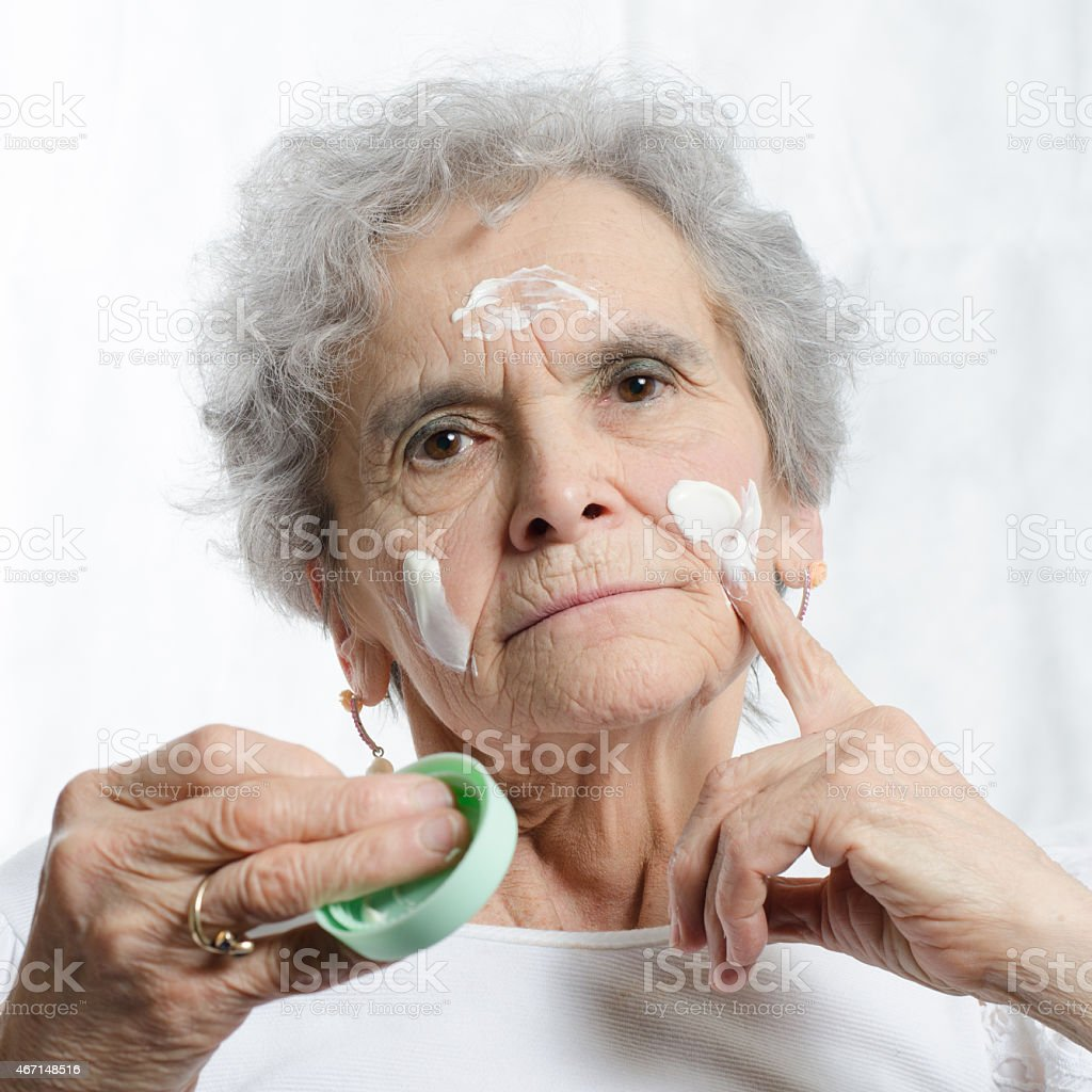 old woman with cosmetics in her face stock photo