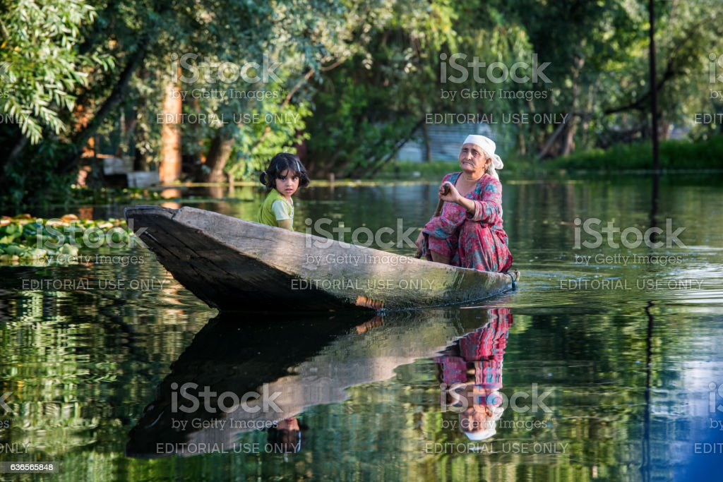 Old woman with girl in a boat, Lake Dal, India stock photo