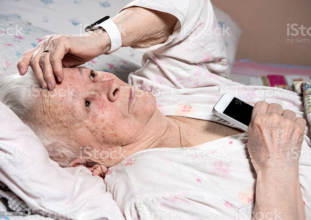 Old woman with smartwatch and smartphone stock photo