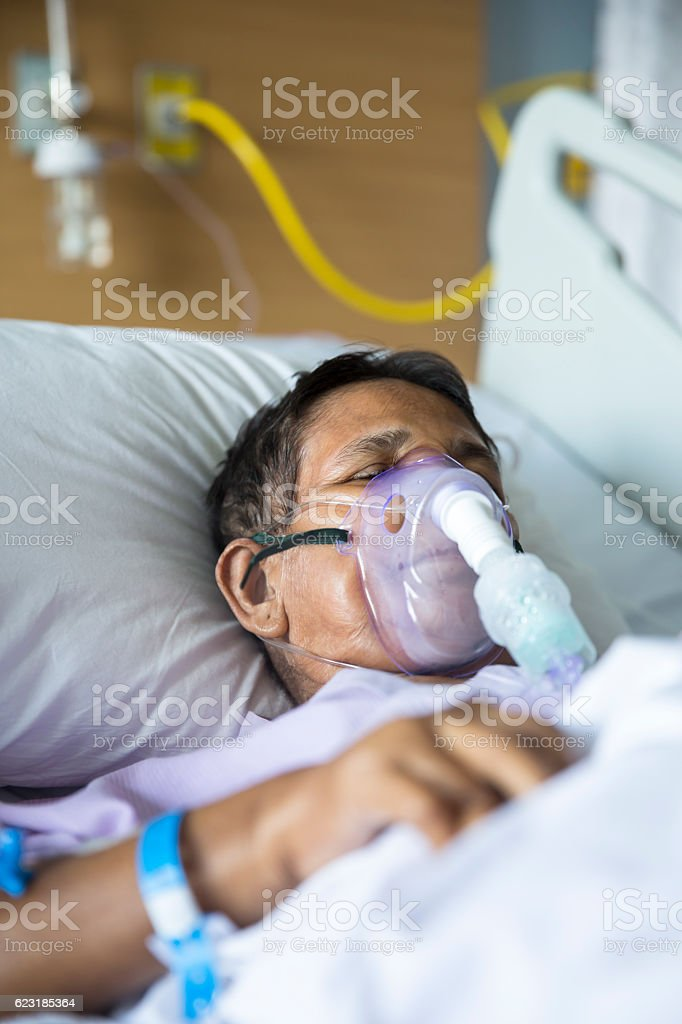 Old woman with Ventilator mask on Hospital bed stock photo