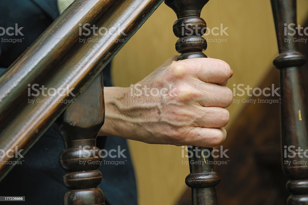 old woman wrinkled hands hold the handrail stock photo