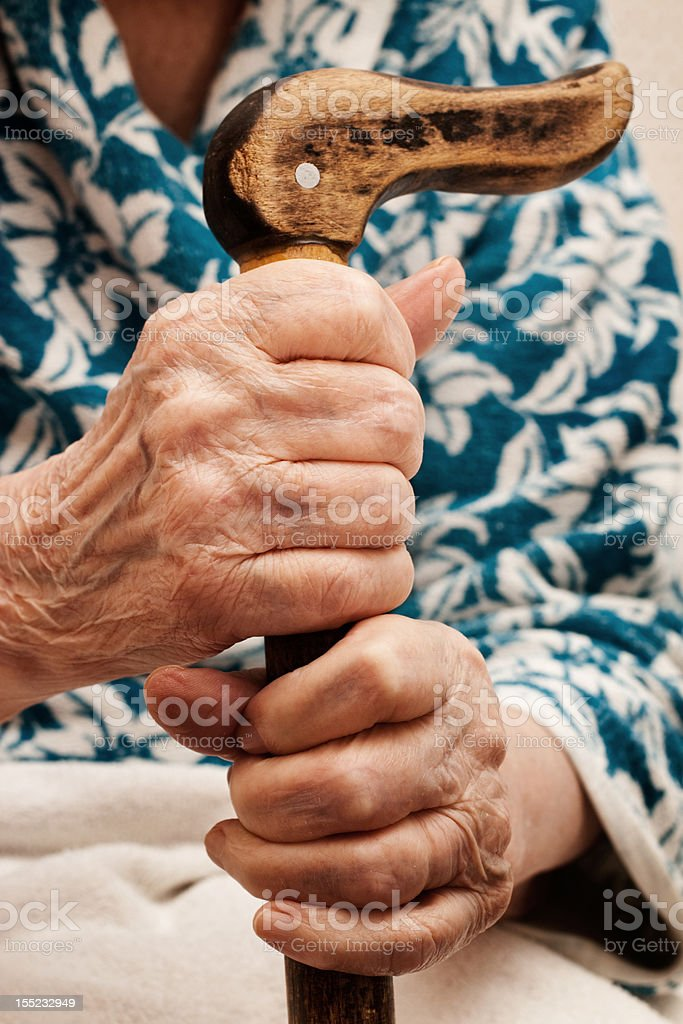 old woman's hand holding a stick stock photo