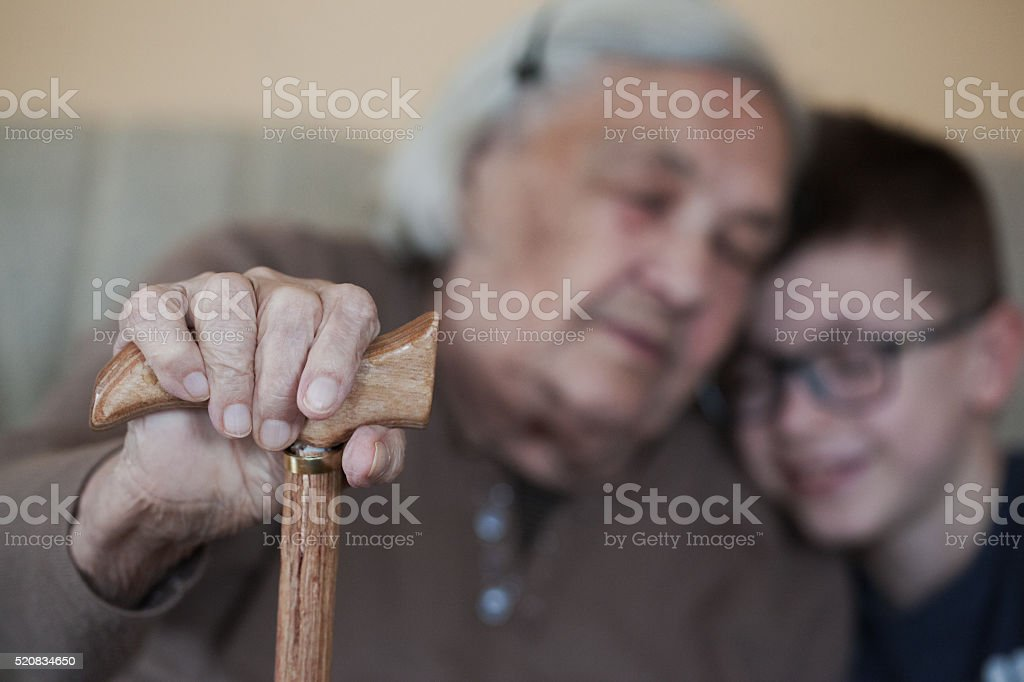 Old woman's hand with grandmother and grandson in background stock photo