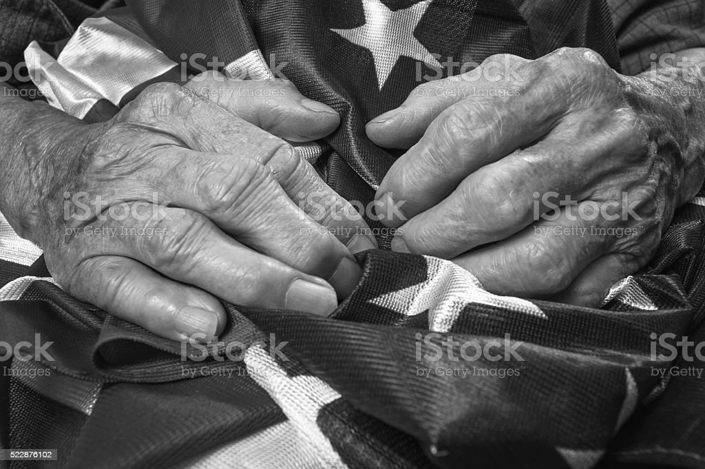 Old woman's hands holding an American flag. stock photo