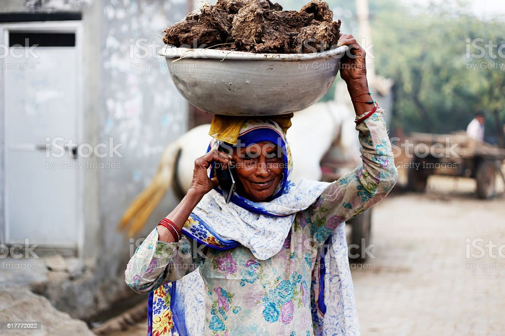 Old women carrying cow dung and talking on phone stock photo