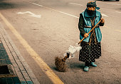 Old women janitor cleans the road in Baku.