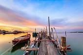 Old wood bridge for small fishing boat with sunset