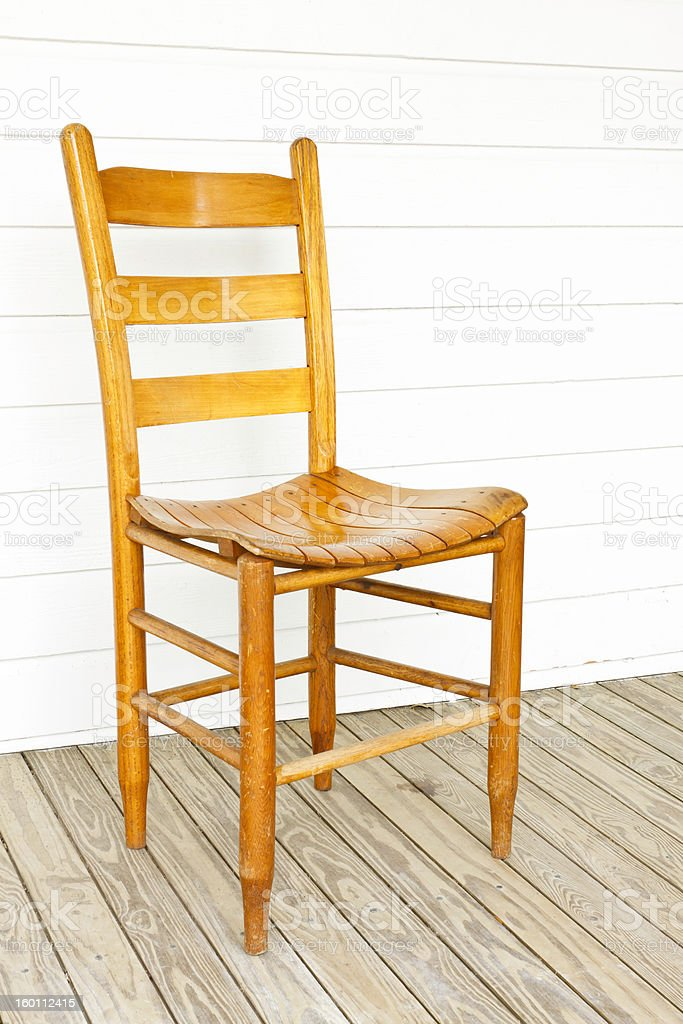 Old Wood Chair On Porch Of White Farmhouse stock photo