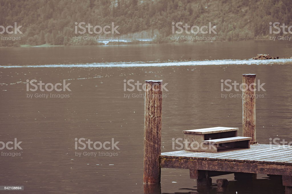 Old wood pier on the lake in vintage.Selective focus. stock photo