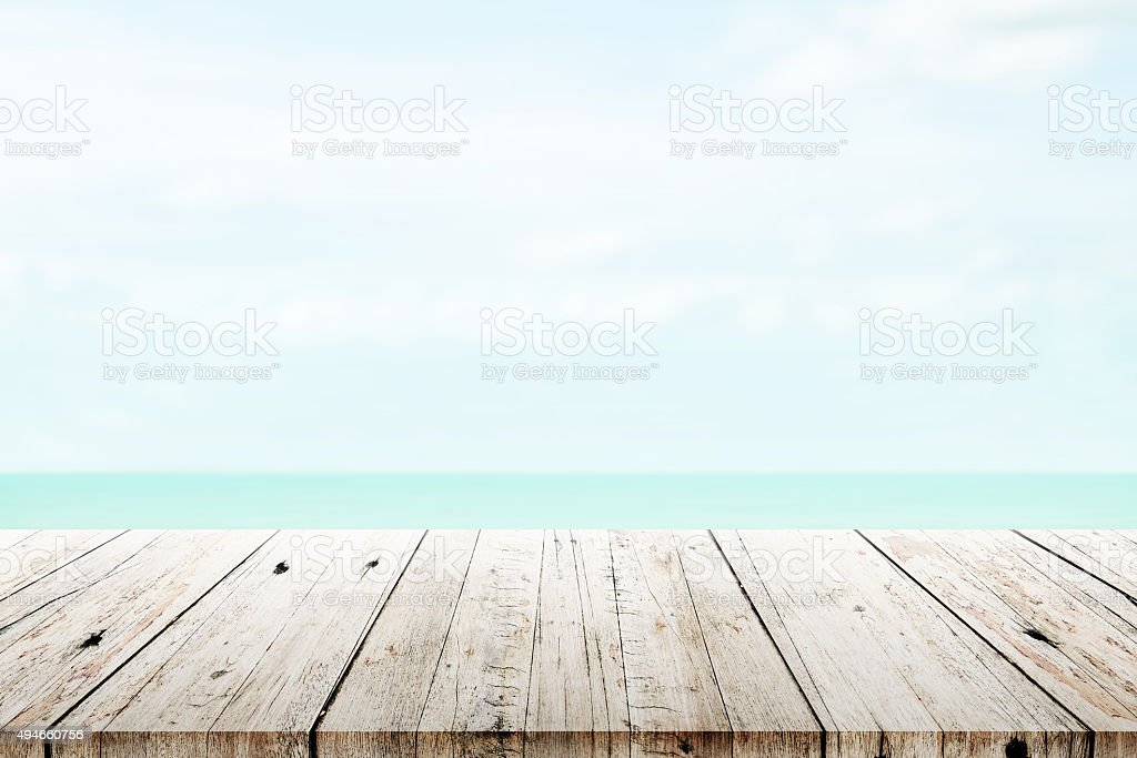 old wood table top on blurred beach background stock photo