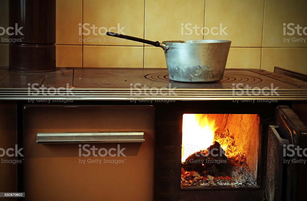 old wood-burning stove in the kitchen of ancient home stock photo