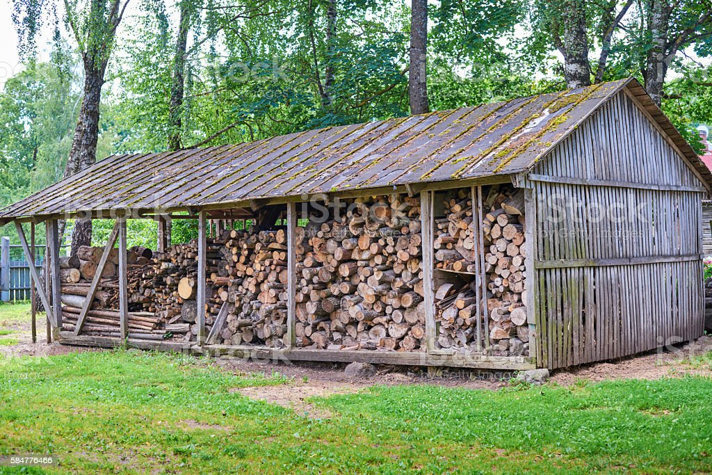 old wooden barn with firewood and a ladder stock photo
