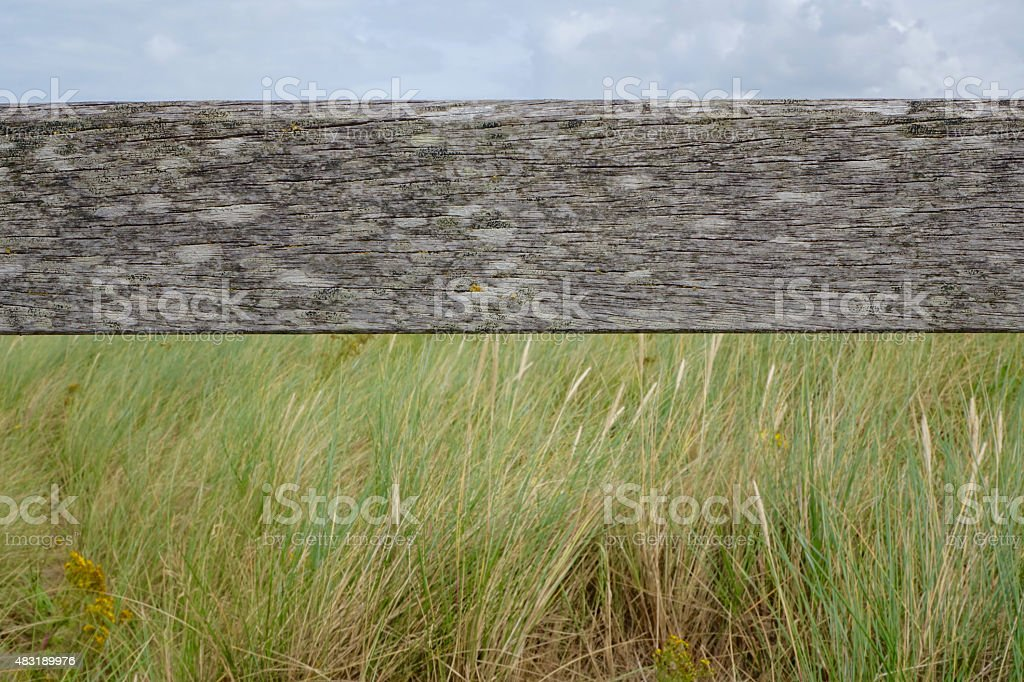 old wooden beam with grass and sky stock photo