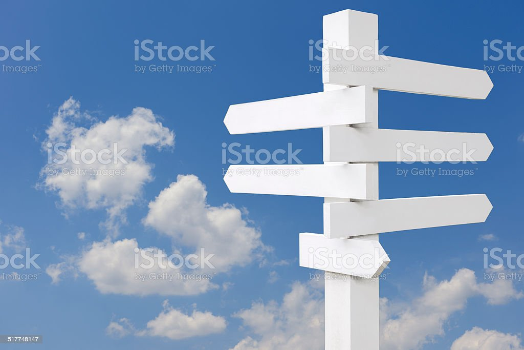 Old wooden blank road sign against blue sky stock photo