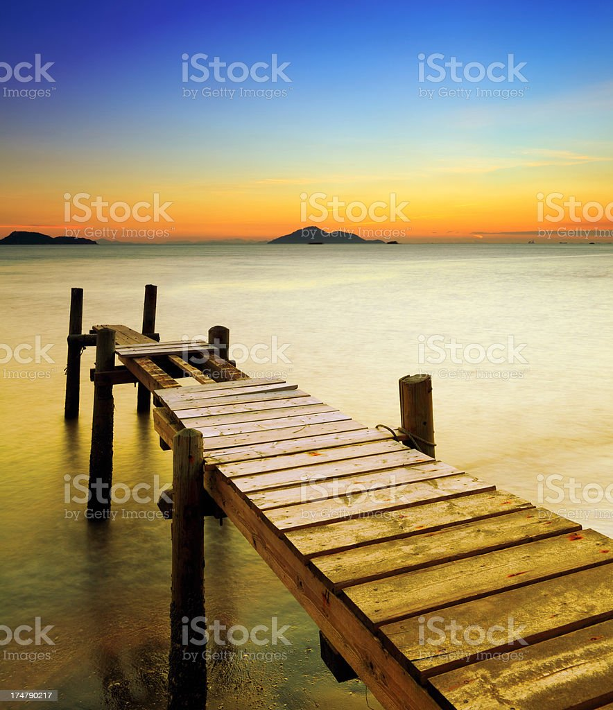 Old wooden boardwalk pier at sunset royalty-free stock photo