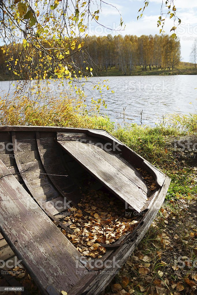 Old wooden boat at the autumn riverbank royalty-free stock photo