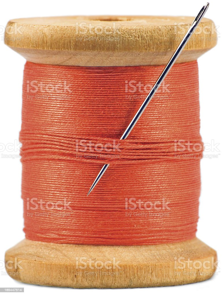 Old wooden bobbin, sewing needle, red thread isolated macro closeup royalty-free stock photo