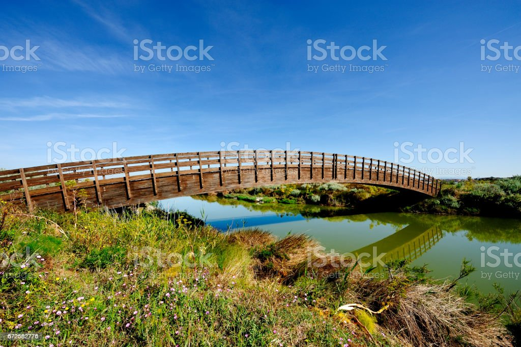 Old wooden bridge over a watercourse that runs quiet. stock photo