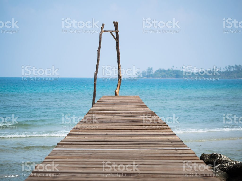 Old wooden Bridge to the blue sea stock photo