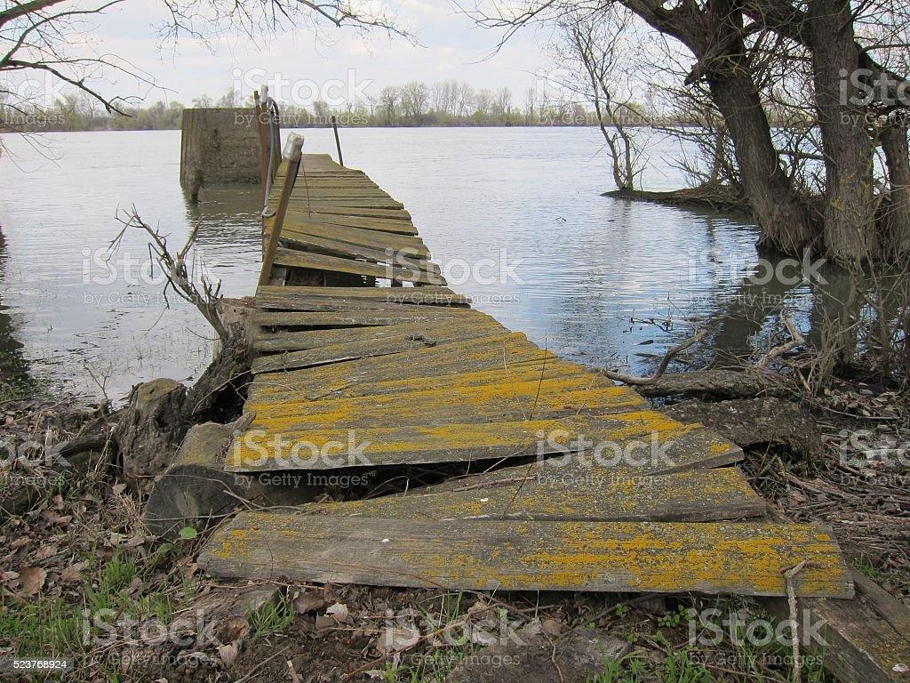 Old wooden broken bridge on island on Danube river stock photo