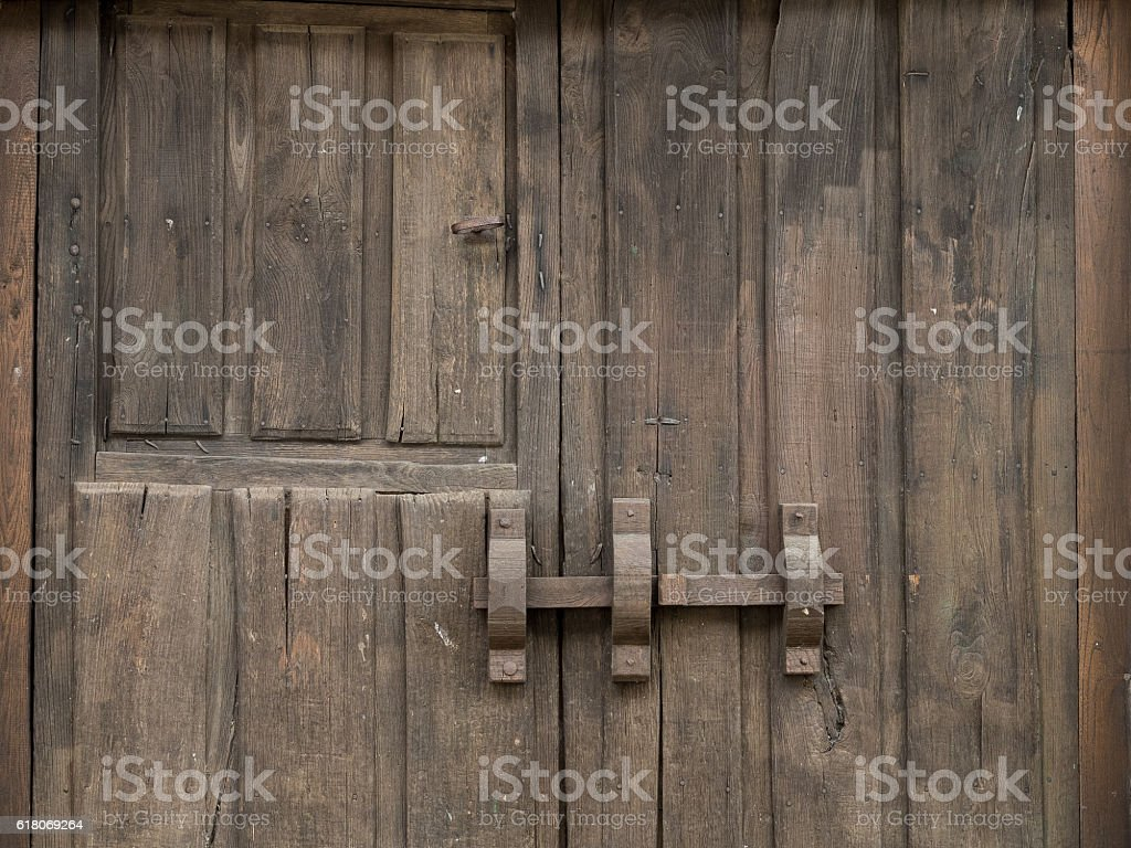 Old wooden brown and rustic gate with a big bolt stock photo