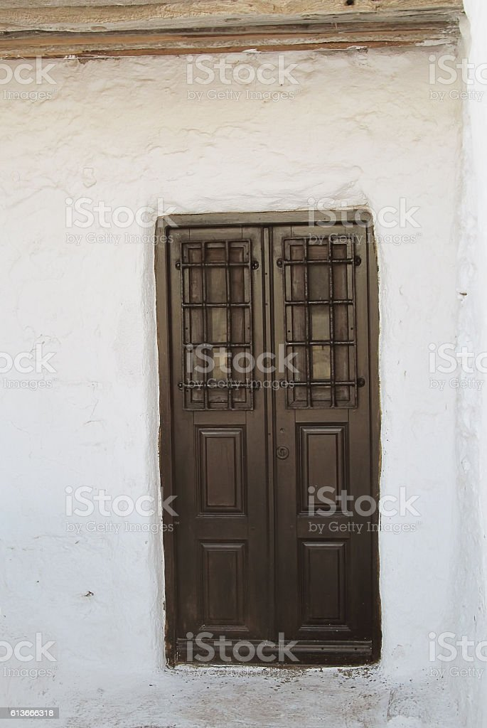 old wooden brown door of a whitewashed building stock photo
