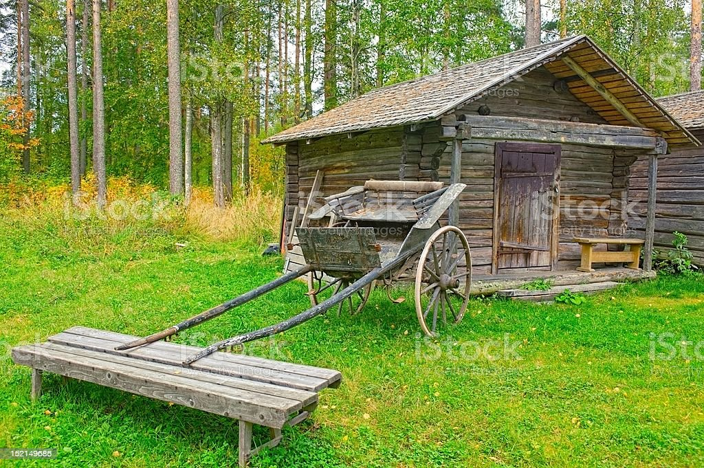 Old wooden cart in front of log barn royalty-free stock photo