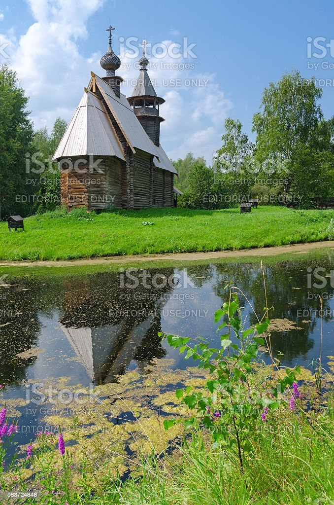 Old wooden church is reflected in water stock photo