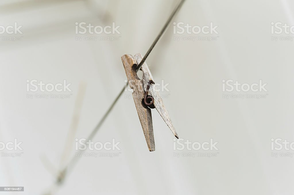 old wooden clothespeg hanging on rope. Blur background stock photo