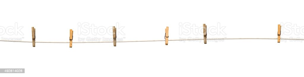 Old wooden clothespins on a rope isolated stock photo