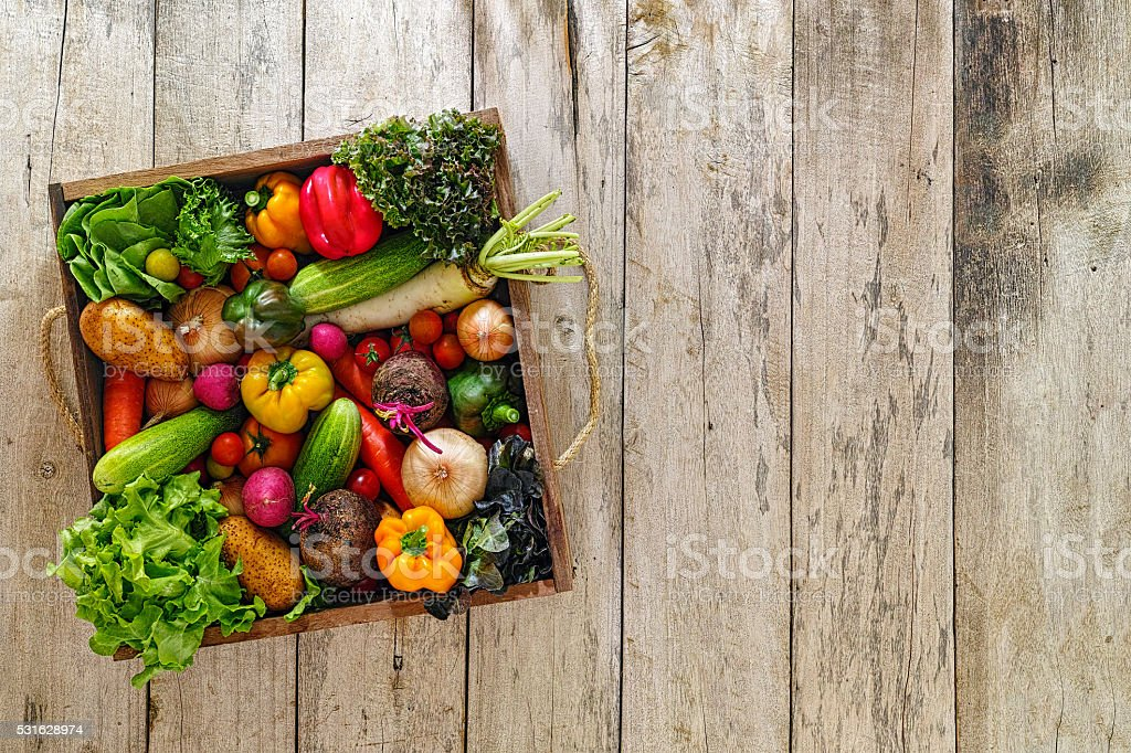 Old wooden crate packed full with fresh market salad vegetables. stock photo