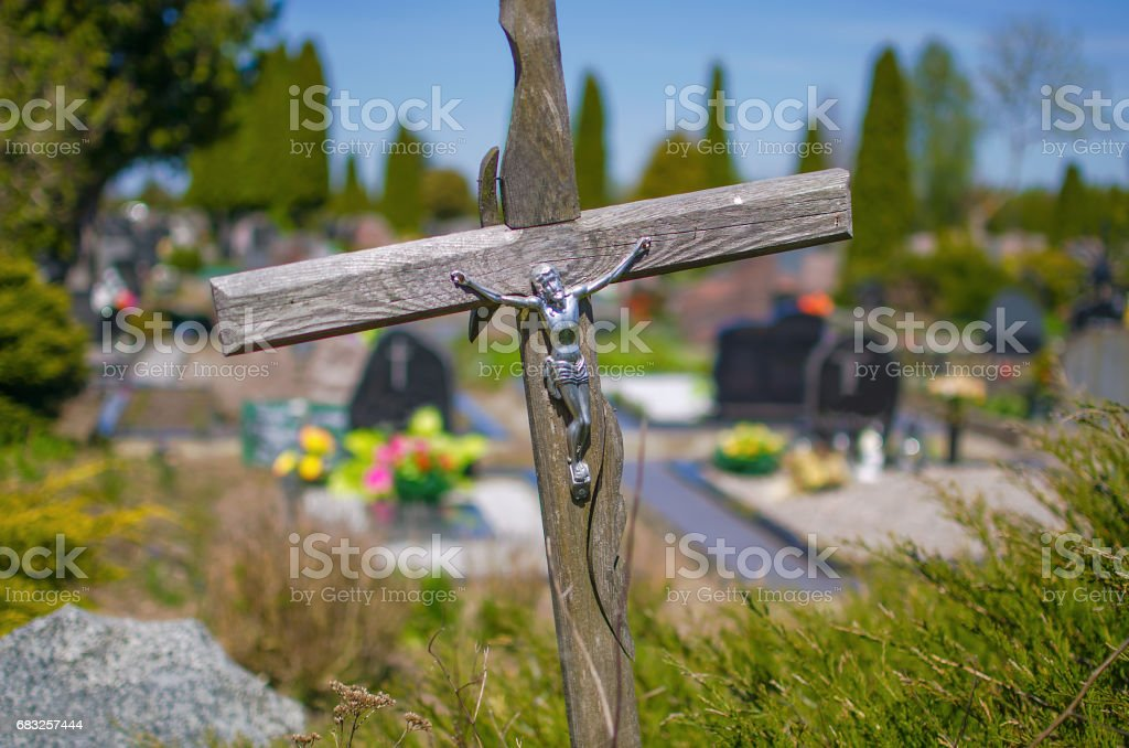 Old wooden cross on a grave in a cemetery stock photo