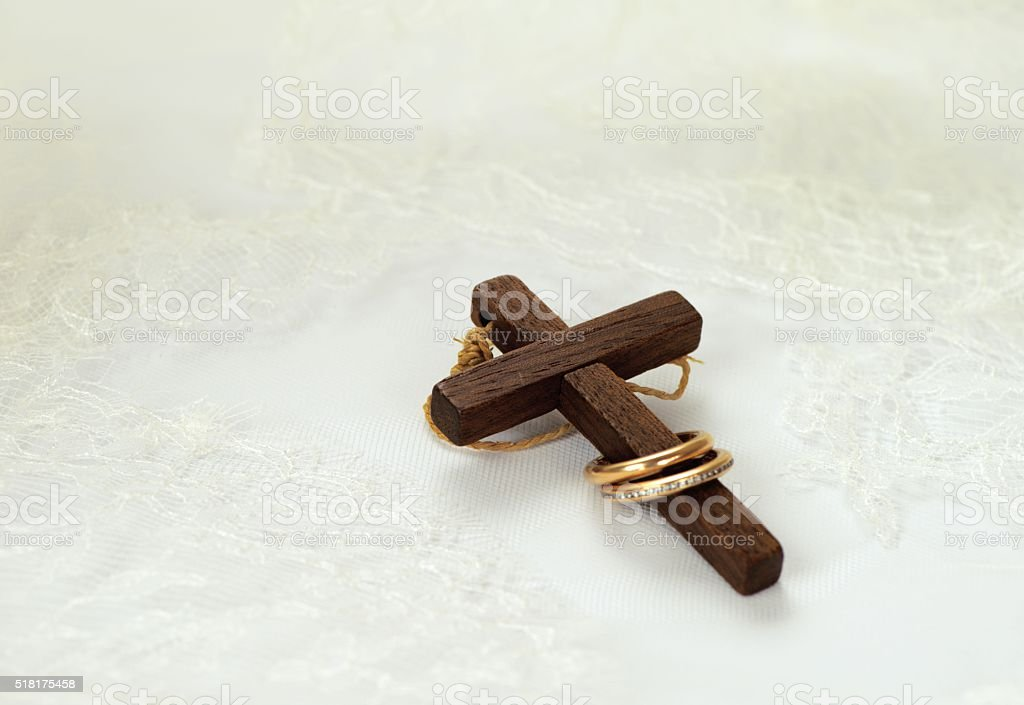 Old wooden cross with two golden rings stock photo