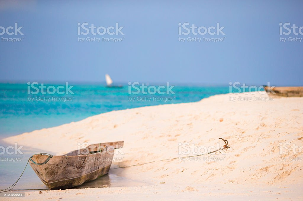 Old wooden dhow on white beach in the Indian Ocean stock photo