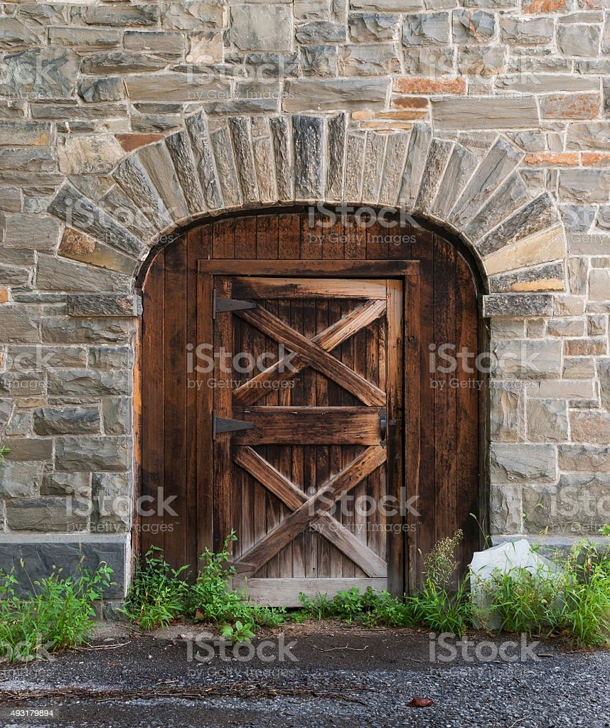 Old Wooden Door in a Barn Stone Wall stock photo