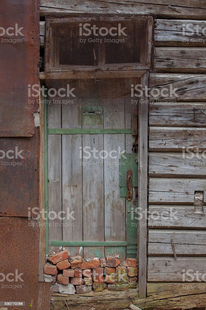 old wooden door in a wall collapsing house stock photo