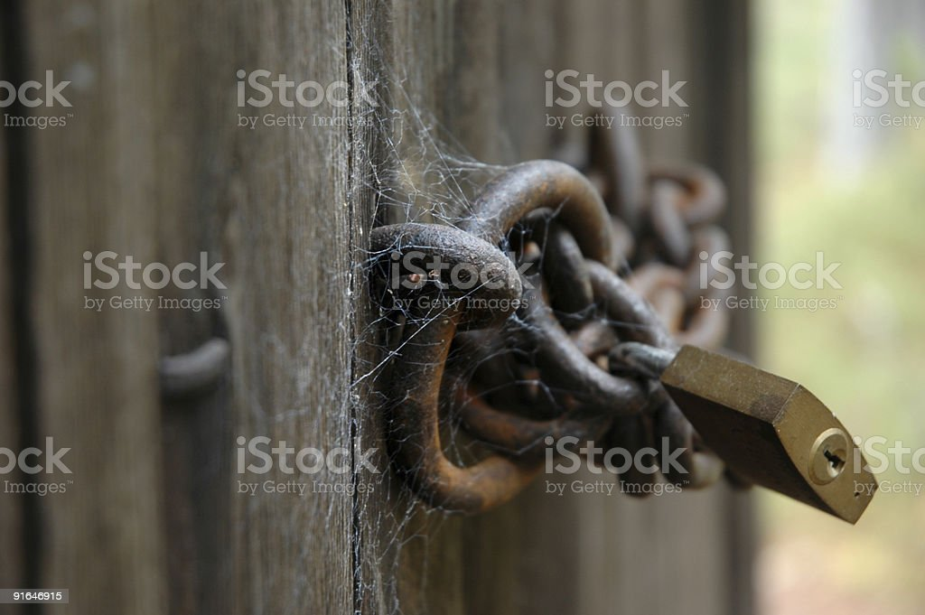 Old wooden door locked with chain and padlock royalty-free stock photo