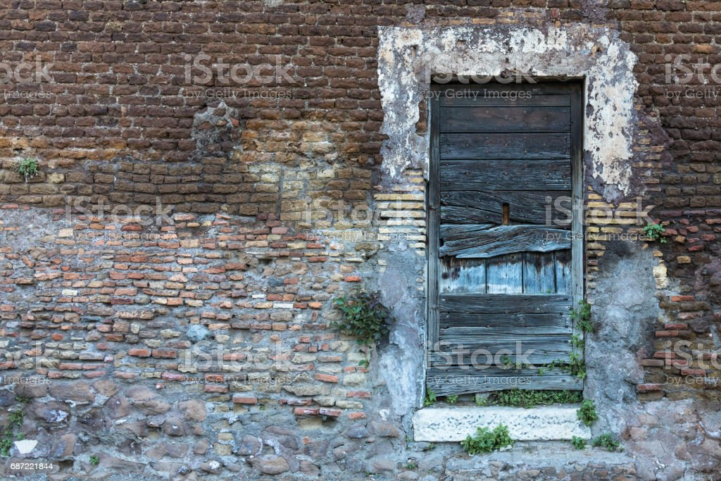 Old wooden door on a brick wall. Left side space stock photo