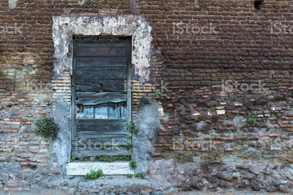 Old wooden door on a brick wall. Right side space stock photo