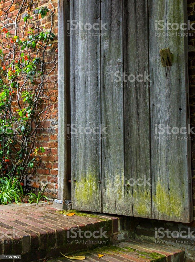 Old Wooden Door Opens to a Forgotten Garden stock photo