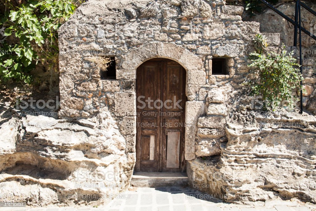 Old wooden door to a stone basement in a Greek house. stock photo