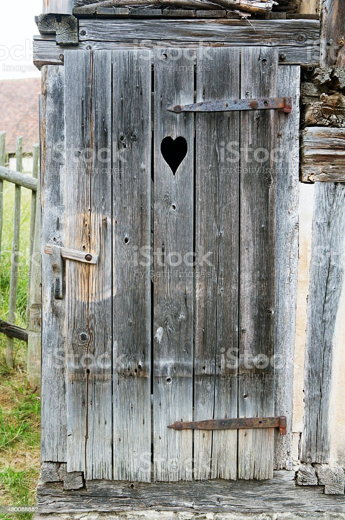 old wooden door with a carved heart stock photo