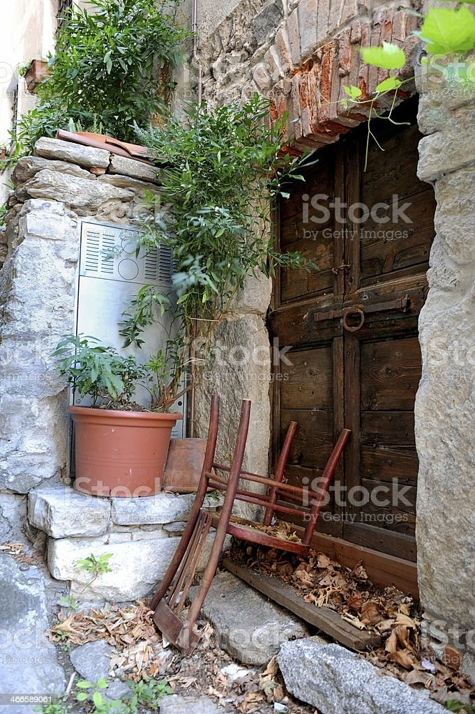 Old wooden door with latch and upside down chair royalty-free stock photo