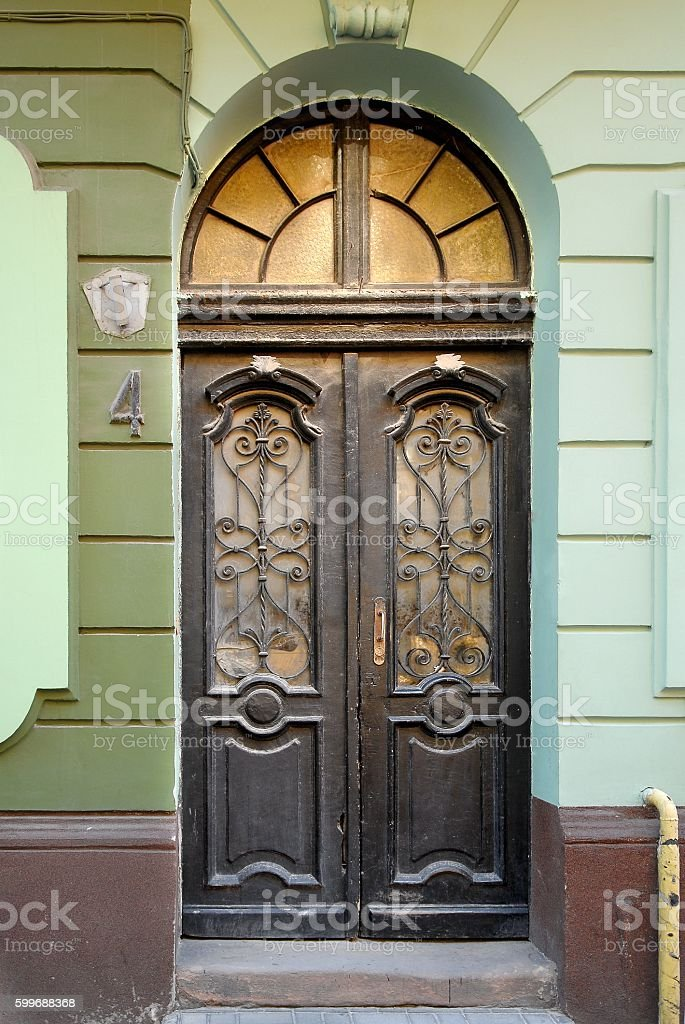 Old wooden doors with stained-glass windows, forged grills and ornaments stock photo