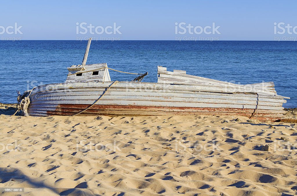 old wooden fishing boat  lying on a seashore royalty-free stock photo