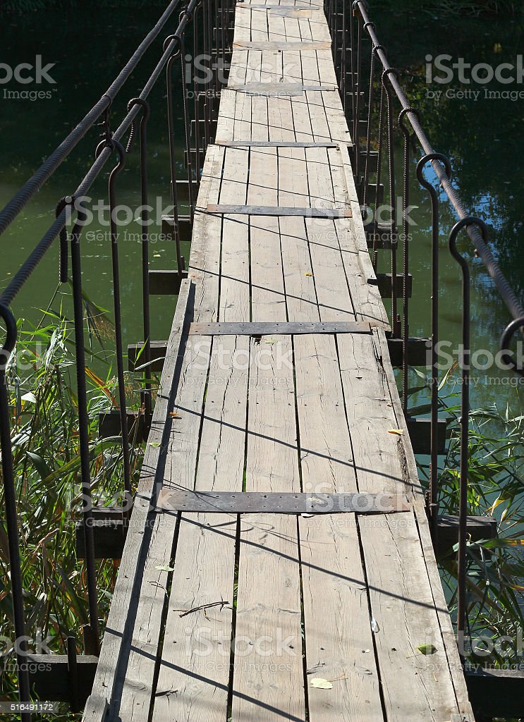 Old wooden footbridge hanged across a small river stock photo