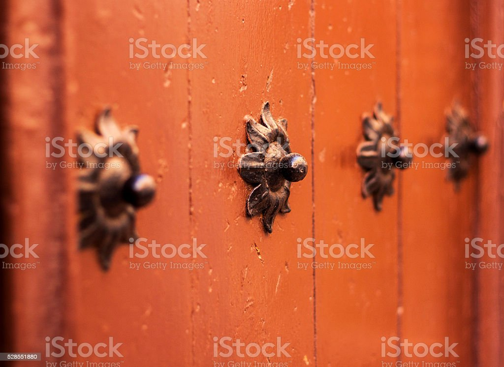 Old wooden gate fixed with large brass rivets in Catalonia, stock photo