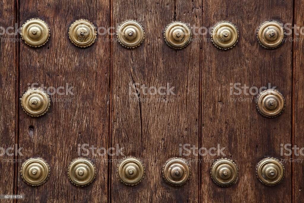 Old wooden gate fixed with large brass rivets stock photo