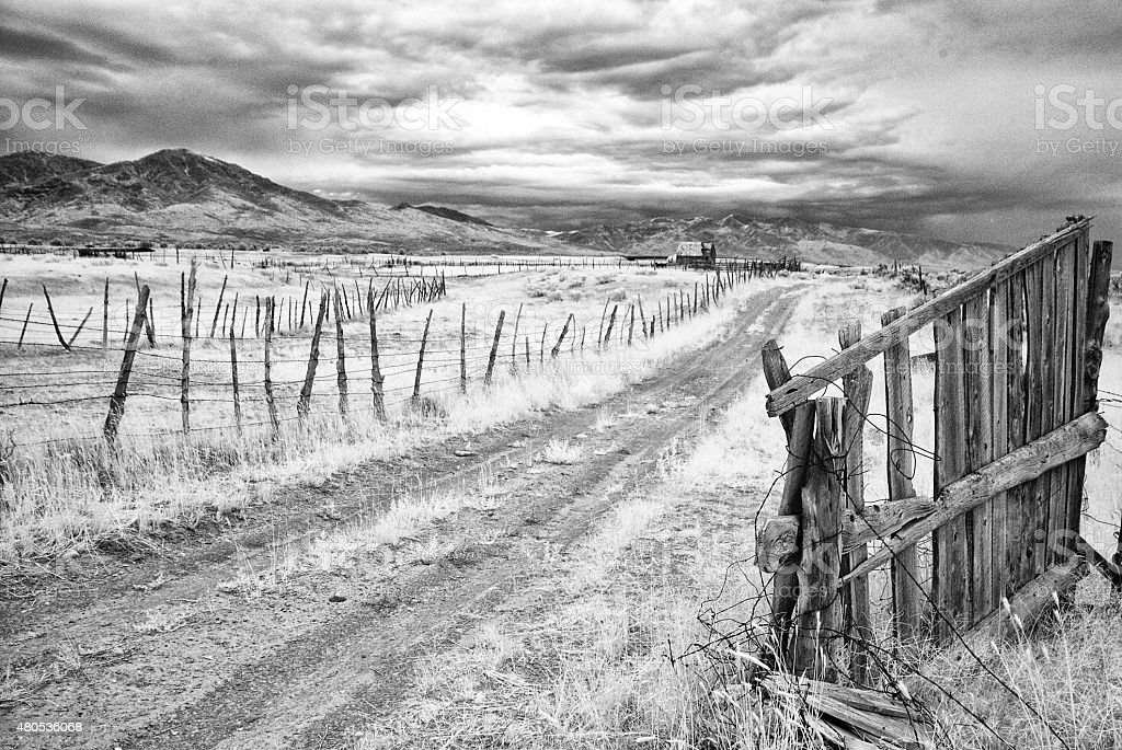 Old Wooden Gate Opens to Dirt Pasture Road - Infrared stock photo